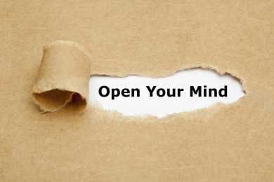 Open Your Mind appearing behind torn brown paper.